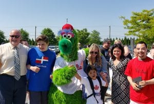 children and teachers pose with mascot